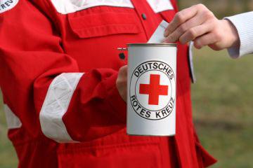 Foto: Eine Hand steckt einen Geldschein in eine Spendendose mit Rotem Kreuz.